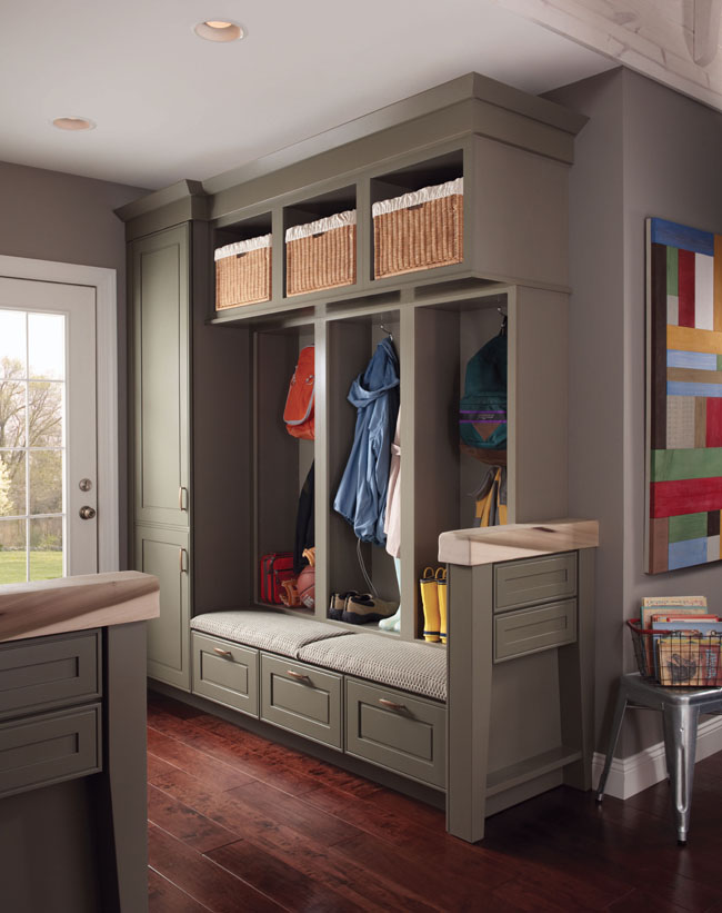 Garrison Square Maple in a duo of Sage and Mushroom finishes brings the look of other rooms into this comfortable and functional mudroom/entryway. Cabinets, shelves with baskets and coat hooks limit clutter while providing easy access to shoes, backpacks, and other out-the-door essentials.