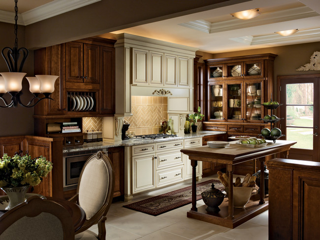 A cooking zone finished in Canvas with Cocoa Glaze takes center stage in a kitchen that features an island, hutch and cabinetry in Chocolate finish.