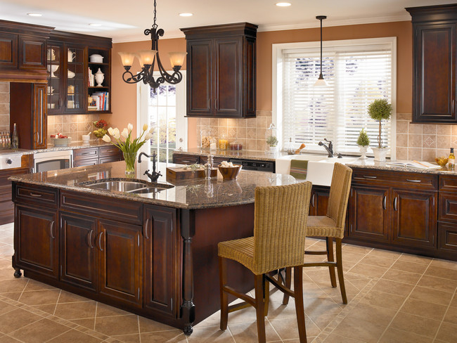 Crown molding, turned legs, and mullion glass doors add refined architectural detail to this cherry cabinetry.
