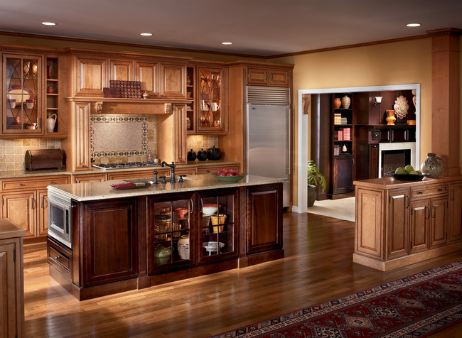 Warm cherry makes this island pop in a maple Praline with Mocha kitchen. Display dishware in glass doored cabinetry with interior lighting.
