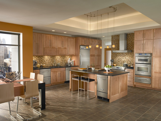Maple cabinetry in Toffee wraps around steel appliances to create a contemporary kitchen.