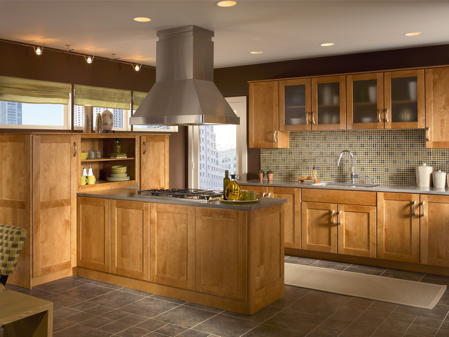 Maple cabinetry in light Praline is accented by moiré glass to softly reveal serving ware in this casual kitchen.