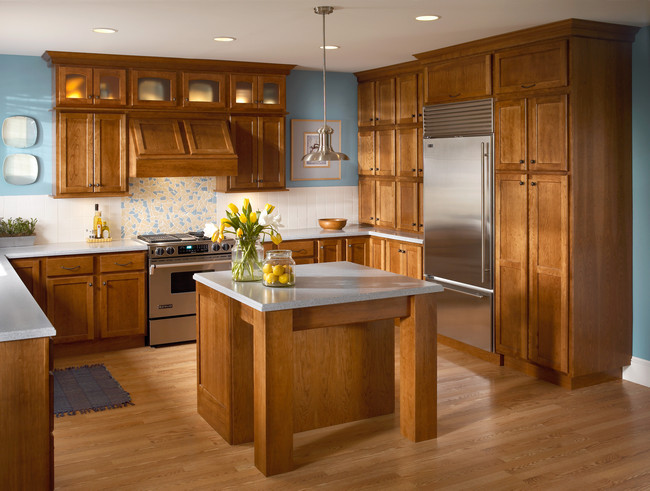 Cherry cabinetry in warm Sunset surrounds the refrigerator simply, yet artistically in this mission inspired kitchen.