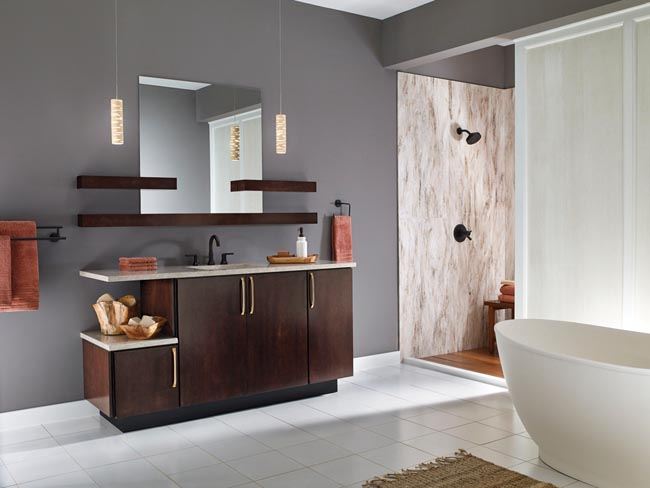 The hero of this bathroom is the Brockton Maple vanity in Peppercorn stain. The slab door, extended countertop, and brushed bronze hardware create clean, contemporary lines for a truly stand-out piece, while painted walls and stark white floor tiles heighten the drama without competing for attention.
