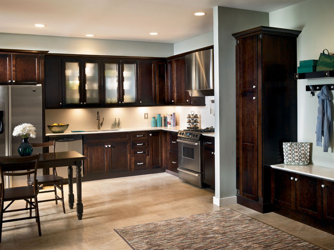 This understated contemporary kitchen features Lyndale cabinetry in Cherry Peppercorn, which offers a warm balance to the stainless appliances. Bold hardware, glass doors, crown molding, and accent lighting provide the finishing touches.