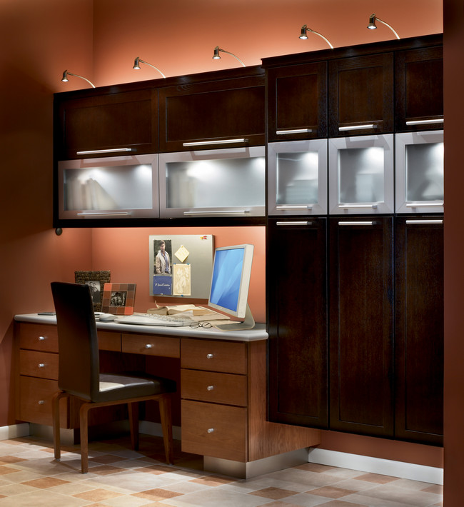 Combine a custom desk in light Toffee with overhead cabinets in dark Quartersawn Oak Peppercorn with frosted glass and aluminum accents.