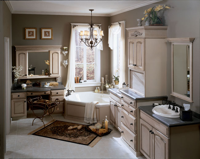 Marquette Maple Roman in Maple Antique Oatmeal with Ebony Glaze gives this master bath a worldly grace. Decorative accents, bronze-finished hardware and faucets, and curving touches in the vanity stool and chandelier add traditional charm.