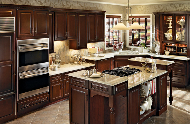 Cherry cabinetry in Burnished Cabernet creates an elegant and inviting place to bake cookies or enjoy a cup of tea in this traditional kitchen.
