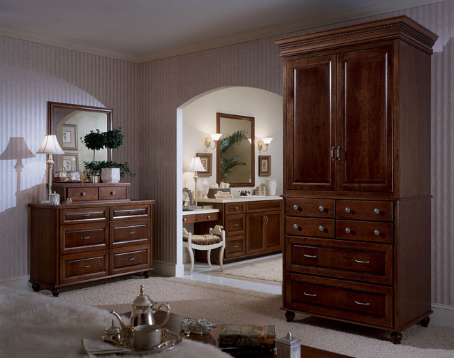 Cherry cabinetry in chocolate with ebony glaze warms up the neutral tones in this master bedroom, visually connecting it to the master bath. Decorative feet and crown molding add a refined touch.