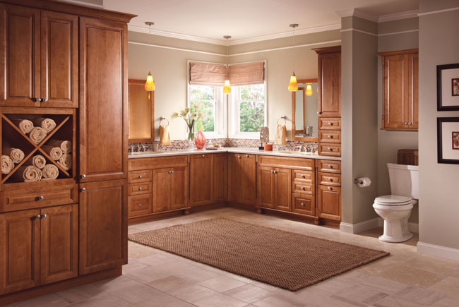 Knollwood Maple Square in Maple Praline casts a warm glow on this luxe transitional master bath. Decorative touches abound in the form of cabinetry feet, metal knobs, and crown molding, and the combination of cabinets, drawer, and storage cubbies keep everything in its place—beautifully.