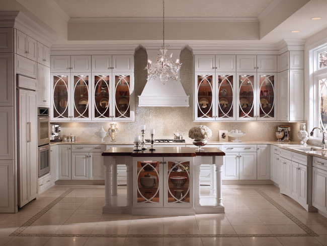 Maple cabinetry in a brilliant Dove White and stunning glass panels gives a contemporary twist on a traditional style in this exquisite transitional kitchen.