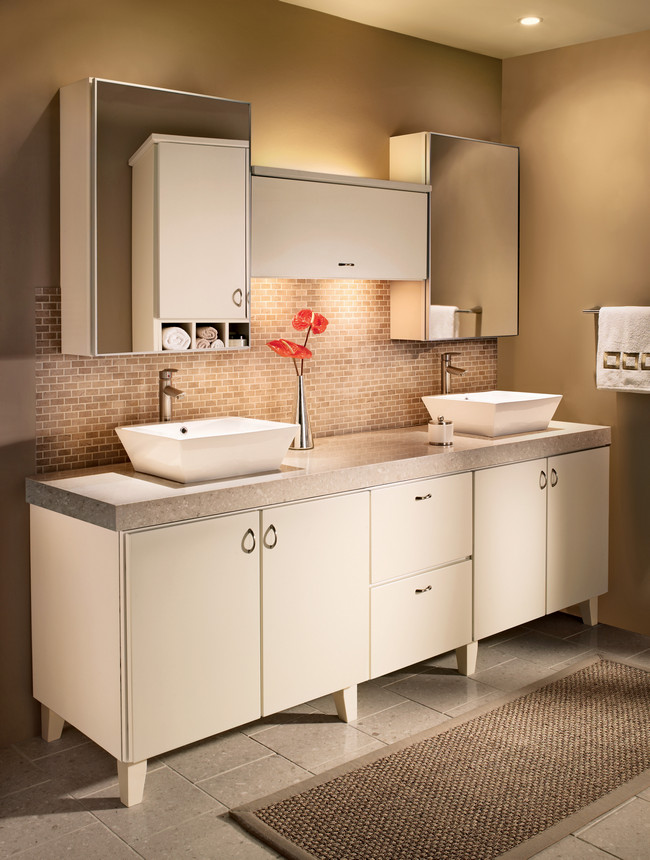 Tapered legs and slab doors in cream Thermofoil create an elegantly modern bathroom for two.