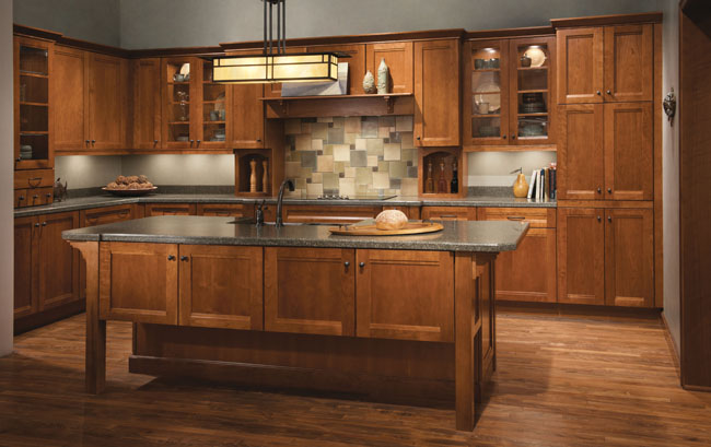 This contemporary kitchen stars Sedona Cherry in Sunset, first in the long L-shaped base and wall cabinets, then repeated in the substantive island with bar seating. Glass doors, spice drawers, and decorative accents call attention to the sophisticated style.
