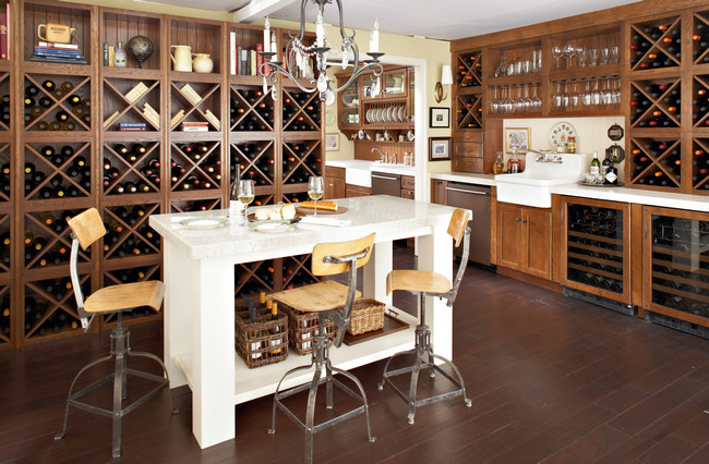 A contrast of finishes in the tasting island and bottle bins combine Old World tradition with uptown style in this spacious kitchen.