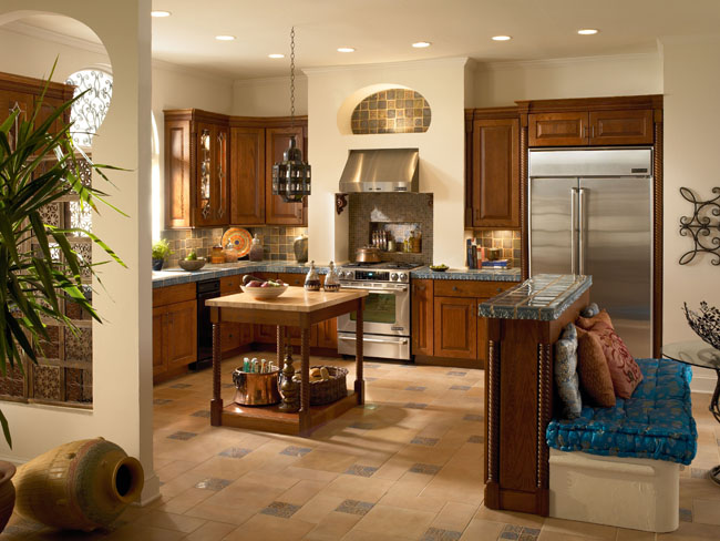 A contrast of textures gives this kitchen its informal grace. Westboro Oak in Autumn Blush, with architectural details of turned legs, glass doors, and crown molding, provide a rich wood texture that contrasts beautifully with the rustic tile, sleek stainless, sculptural iron accents, and sumptuous fabrics.