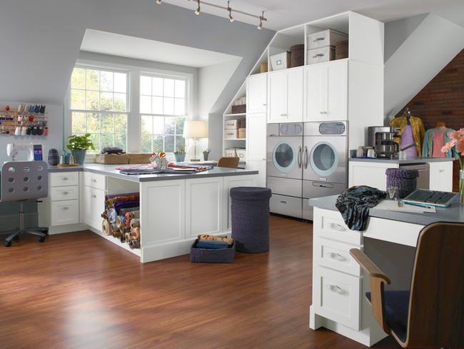 Crisp white cabinetry is accented by muted grey walls to create an intriguing contrast in this spacious craft and laundry room.