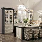 The bold pairing of white cabinet doors and drawer fronts with black crown molding creates striking visual interest in this luxurious kitchen.