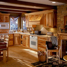 Reveal the natural beauty of hickory in this L-shaped rustic kitchen with base furniture drawer cabinetry and a coordinating wall hood mantle.