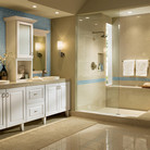 Clean, white Thermofoil cabinetry with tapered legs and elegant recessed panel doors conceal bath essentials and create a spacious coastal retreat.