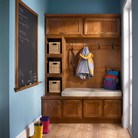 An entryway ensemble in natural cherry creates a cozy corner for the family to take off boots and hang coats.