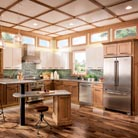 This modern rustic kitchen features Putnam Quartersawn Oak cabinetry in Distressed Ginger, replicating the appearance of reclaimed wood. Wave Glass Inserts in select doors mirror the elegant transom windows and create the appearance of heirloom furniture. The multi-height island provides the option of sitting or standing while preparing food, and invites family members and guests to gather around the chef. Hardware and barstools with antiqued finishes add more lived-in warmth.