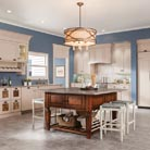 This kitchen offers creature comforts for everyone in the family. Kids and adults can pull up a cozy chair at the island, while the family pet enjoys the convenient in-cabinetry feeding station. The look is achieved by combining Marquette Cherry in Distressed Autumn Blush stain for the spacious island with Cornell Maple in Chai paint for the wall and floor cabinets. An attractive wall hood, elegant crown molding, a space-saving wine rack and antique-styled hardware gives the room a luxurious touch.