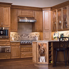 Praline maple cabinets are highlighted by glass doors and wine storage cubbies fo in this warm and comfortable kitchen.