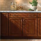 Marquette cabinets in Sunset Cherry warm up the tile backsplash, adding a layer of rich woods to the texture in this traditionally styled kitchen. Accent lighting under the cabinets imparts a cozy glow.