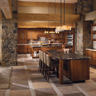 This rustic kitchen reflects its natural setting with warm woods, stone walls, and marble countertops. Dual islands offer plenty of prepping and tasting space, while a bank of glass cabinets display favorite serving pieces.