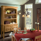 A country inspired oak hutch with open shelving provides easy access to dinnerware and napkins in this casual dining area.
