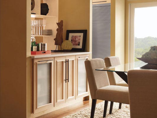 A dining room just off the kitchen continues the streamlined, contemporary look with a buffet/bar and decorative storage featuring Kendrick Maple Square in Parchment.