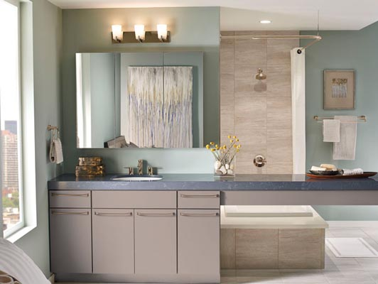 Avery cabinetry in Pebble Grey paint gives this contemporary loft bathroom a calm, sophisticated feel. The Mode Bar Pull in Brushed Bronze adds a touch of warmth to the sleek lines of the slab door and coordinates with the bronze faucets, towel bars and other accessories. An expanse of countertop divides sleeping and bathing areas without obstructing the city view. Behind the scenes, the CoreGuard® Vanity Sink Base stores bath products and cleaning supplies while helping to protect the vanity from minor spills.