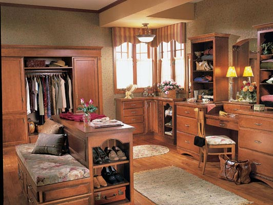 """This bedroom gives new meaning to the term """"walk in closet."""" Hanley in Maple Chestnut lends a worldly grace to the bureaus, dressing table, wardrobe, and bench, creating a comfortable, classic space for dinner dressing."""